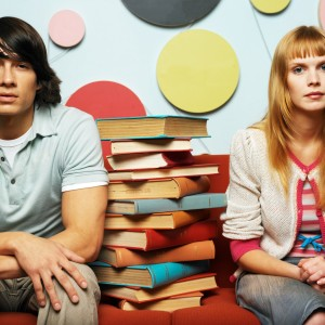 Young Couple Sitting with a Pile of Books